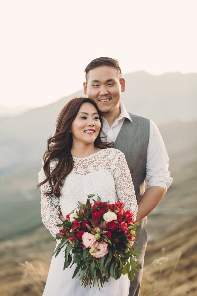 bride in white lace wedding dress with long sleeves and groom with wedding bouquet at queenstown wedding